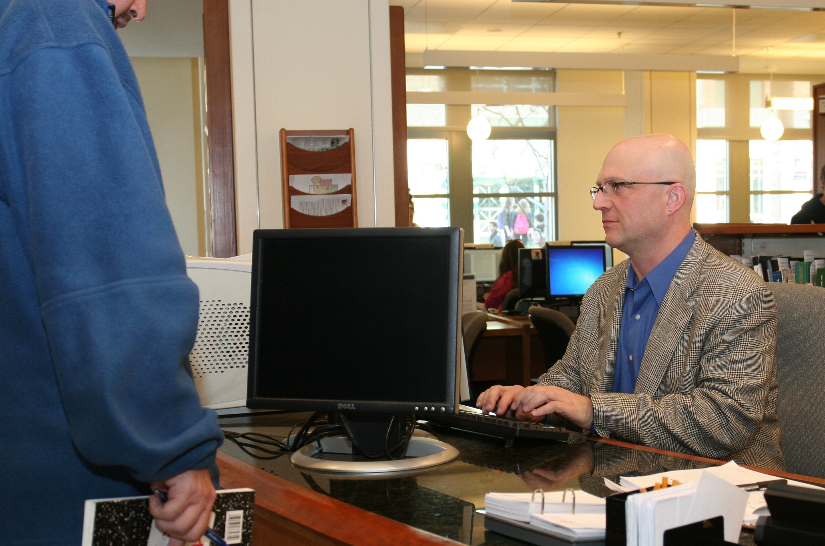 Doug Dechow, Ph.D., sciences librarian, assists a student who stopped by the reference desk for research help. (Photo/David Goto, reference librarian)