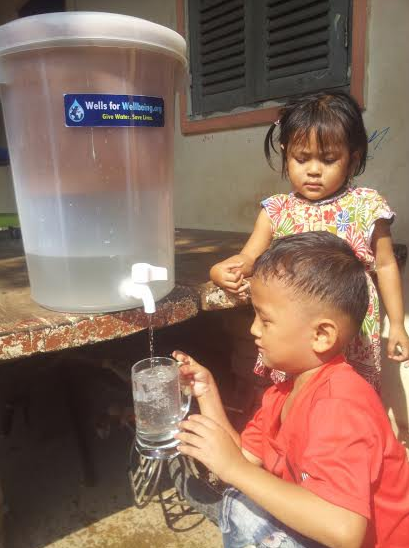 Kyle Kim-E '14, at left in gray shirt, with fellow Wells for Wellbeing volunteers and a family drawing water from their new well for the first time.