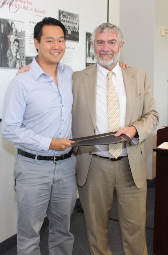 Chancellor Daniele Struppa presents the Senior junior Wang-Fradkin Professorship to Christopher Kim, Ph.D.
