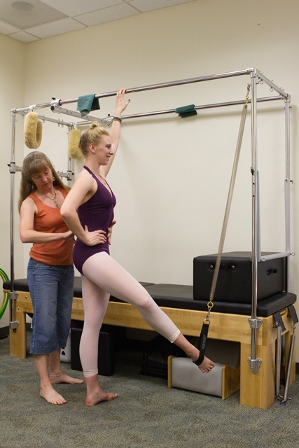 Professor Robi9n Kish helps dancer Mandy Dray '14 warm up before a workout. Kish will be among the presenters this month at an international conference focusing on the health of dancers and other performers.