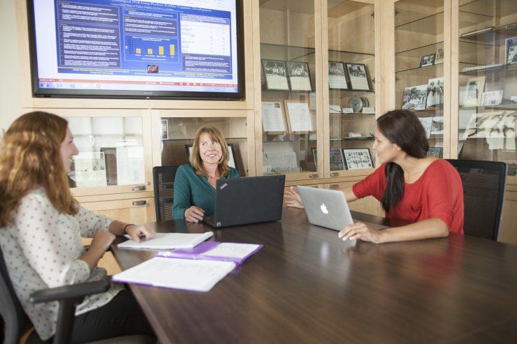 three people at computers
