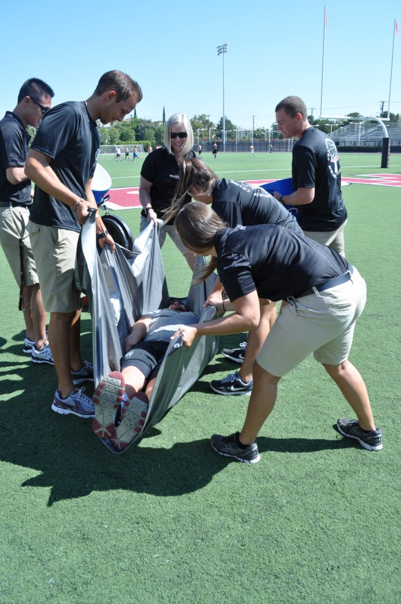 group helping athlete on field