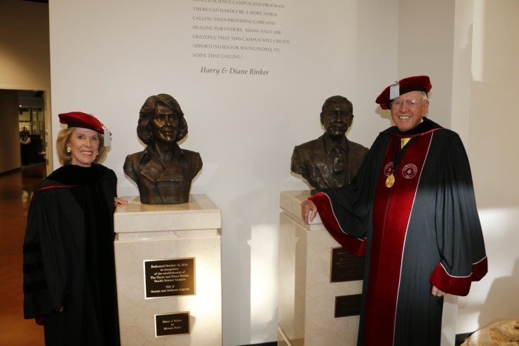 man and woman smiling next to busts