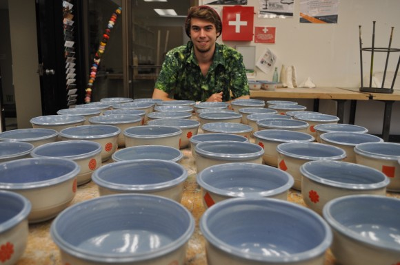 student smiling with pottery