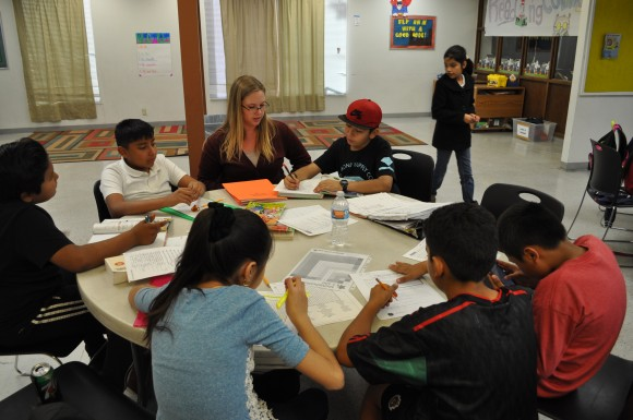 Chapman integrated educational studies major Carley Waterbury '17 guides a table of middle school students through a variety of homework assignments at The Friendly Center.