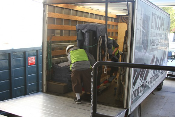 Workers wheel one of Musco Center's new Steinway pianos out of the delivery truck.