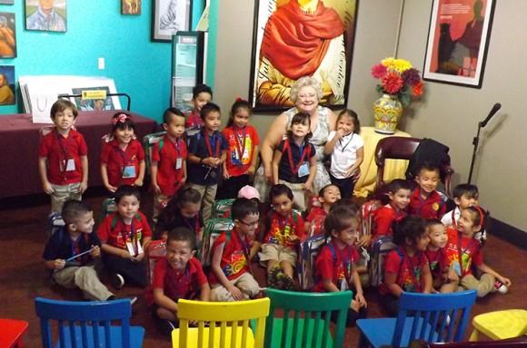 Cristine Cross of the Klein Family Foundation with children at the former Libreria Martinez de Chapman University, now the Centro Comunitario de Educacion.