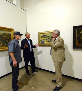 three men talking in art museum