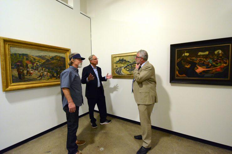 three men talking in art museum