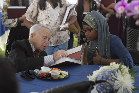 Holocaust survivor signing a book for a woman