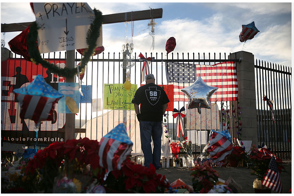 man standing in front of fence filled with memorabilia