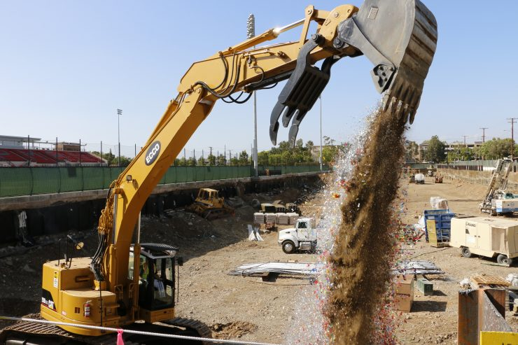 Backhoe pouring dirt