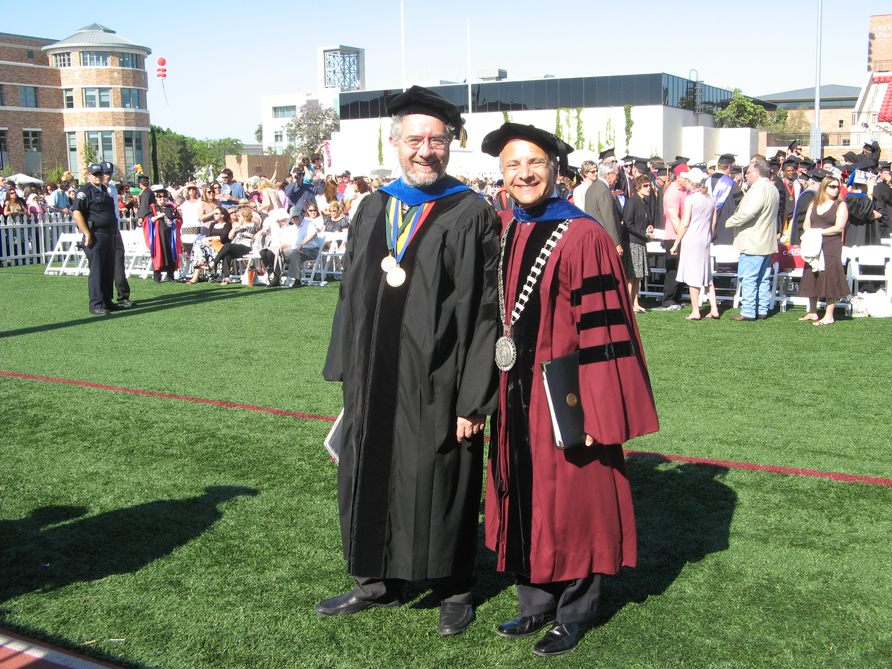 two men smiling in graduation gowns