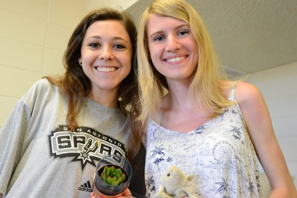 Two young women holding a small plant and a small stuffed animal