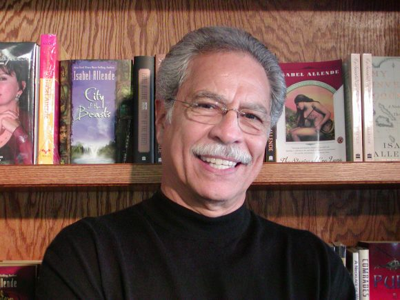 Smiling man with mustache in front of bookshelf.