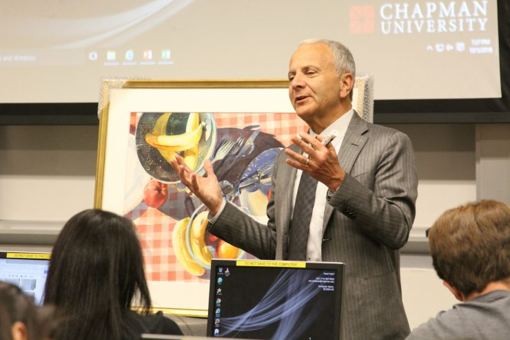 President Emeritus and Professor Jim Doti teaches statistics with the aid of a painting from Chapman's Hilbert Museum of California Art.