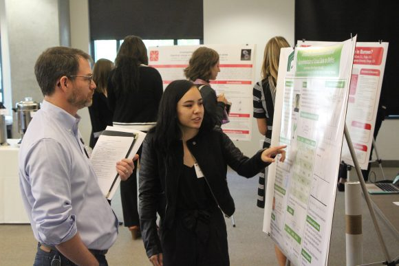Christine Navarro explains her poster to Dr. Jason Keller