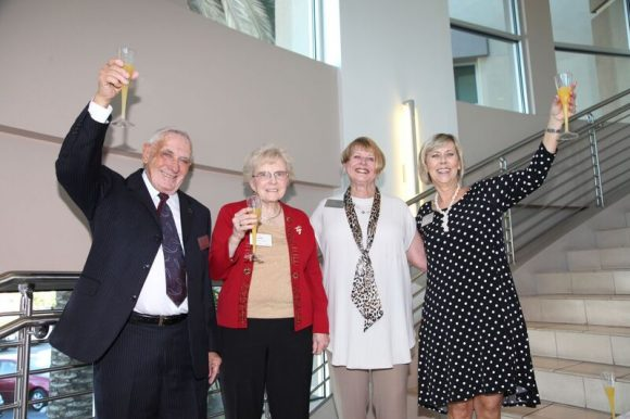 one man and three women - holding champagne classes up for a toast and smiling