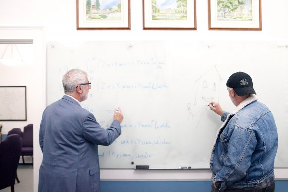 Chapman President Daniele Struppa writing on white board with twin