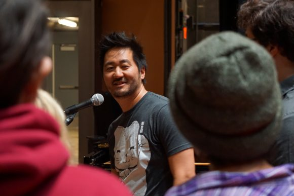 Kishi Bashi at microphone smiling at students