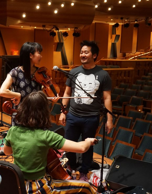 Students Lisa Yoshida and Bella Pepke, with violin and cello, learn how to operate loop pedals from Kishi Bashi.