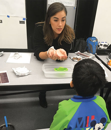 Graduate Student Maribel Barrios Teaching Math to a child at Salk Elementary