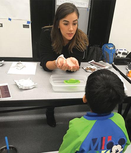 Graduate Student Maribel Barrios Teaching Math to a child at Salk Elementary