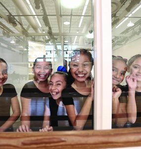 Student dancers from Wooden Floor gather in studio.