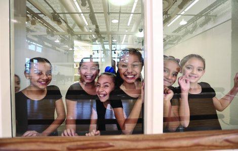 Student dancers from Wooden Floor gather in studio.