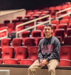 Miguel Mendoza '24 sits in Folino Theater at Marion Knott Studio.