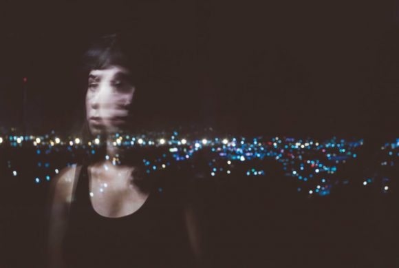 Photograph of blurred girl in front of border at night.