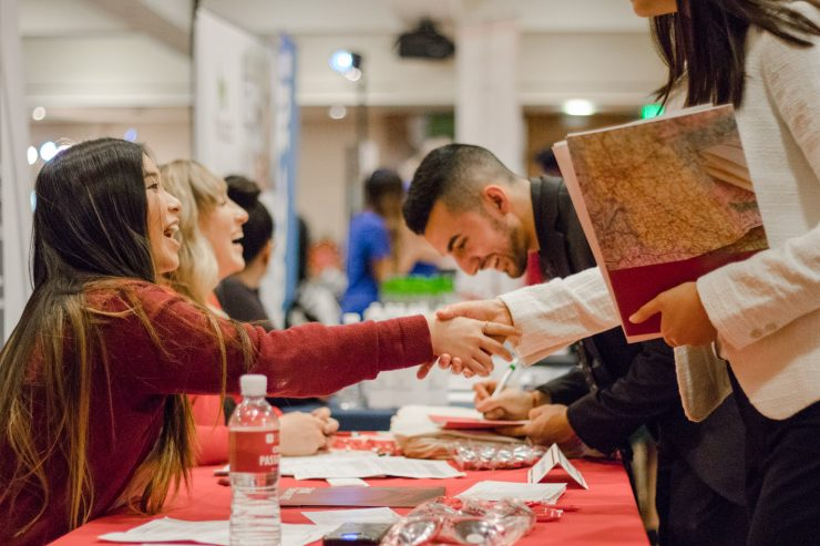 Students shake the hands of potential employers at the career fair.