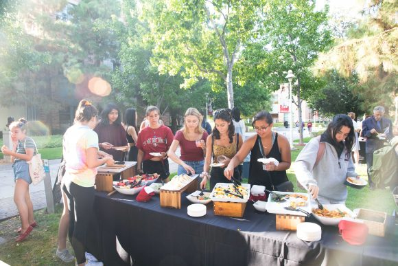 Students take food from an outside table.