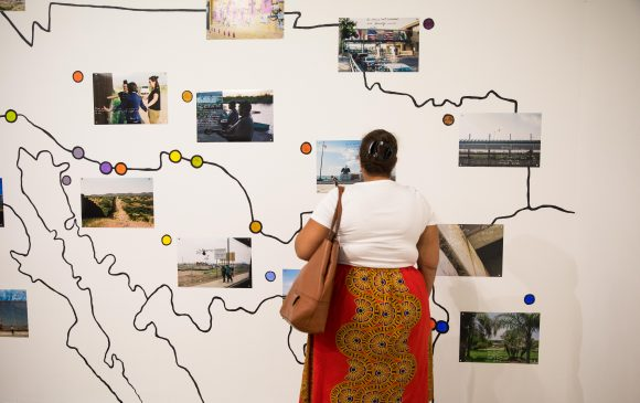 A woman in front of an artwork resembling a map.