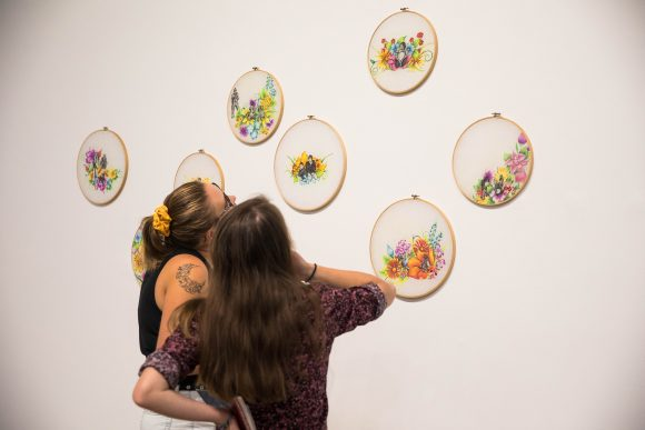 Women look at embroidery hoop artworks.