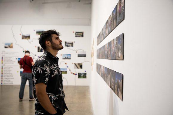 Man looks at artwork.