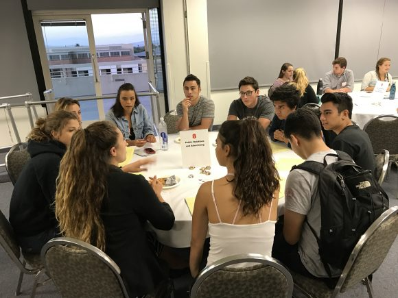 Students discuss at a round table.