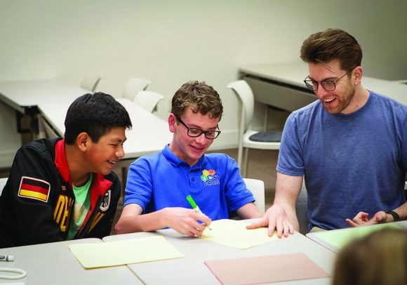 Middle-school students Sam and Nathan share a laugh with their Chapman mentor, James Francese '19, who earned degrees in math and philosophy being diagnosed with ADHD.
