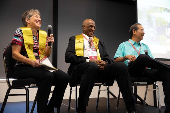 Karen Wilkinson, Frank Franklin, Cliff Ishigaka seated on stage laughing