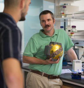 Biological sciences student Alex Drives '21, left, talks with Carter Berry, Ph.D, about equipment Drivas helped design to advance Berry's plant research. Photo by Dennis Arp.