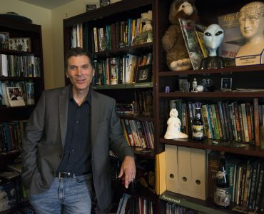 Chris Bader smiles in front of his bookshelf