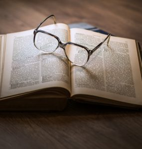 Book on table with glasses.