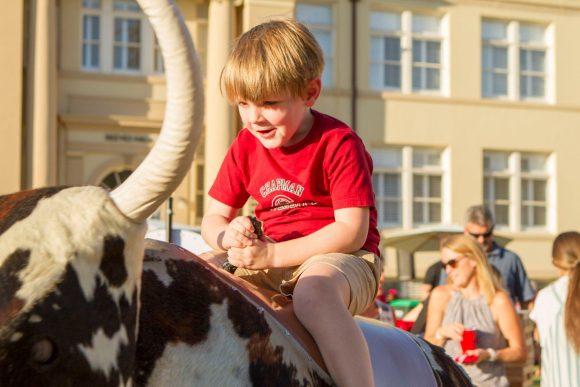 Boy in Chapman t-shirt on mechanical bull