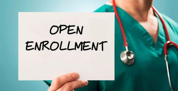 Image of a doctor holding an open enrollment sign.