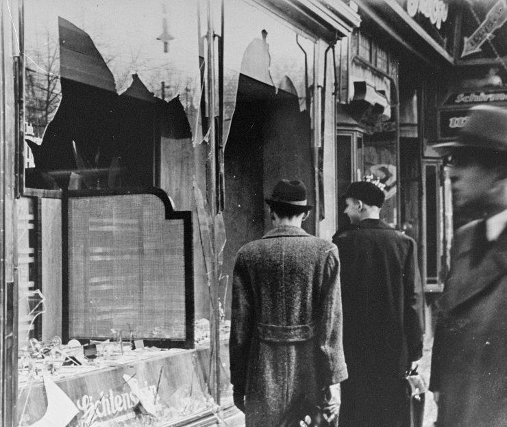 Men in hats walk past broken windows