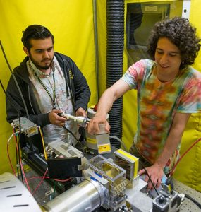 Researchers standing over electronic device