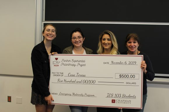 four people and a giant check