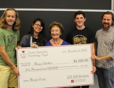 five people with giant check