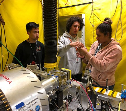 Student team stands around laser