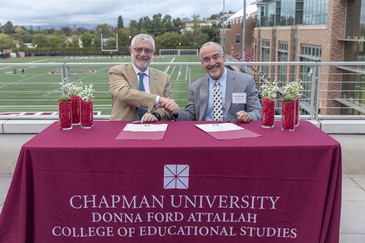 Daniele Struppa and John Hernandez shakes hands at table